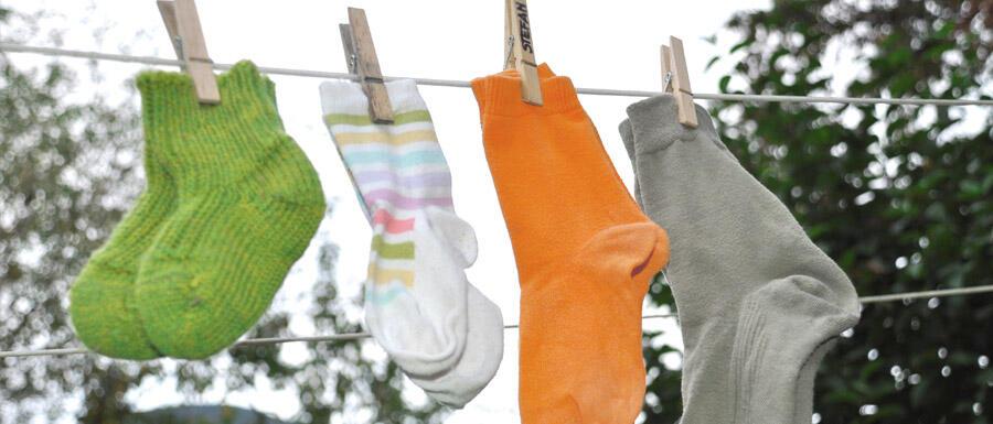 4 Paar bunte Socken von Kindern und Erwachsenen hängen auf einer Wäscheleine © Robin Menges