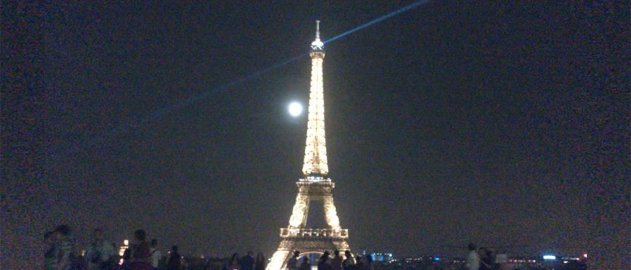 Eiffelturm in der Nacht vor Vollmond. Im Vordergrund sind Menschen zu sehen. © Robin Menges