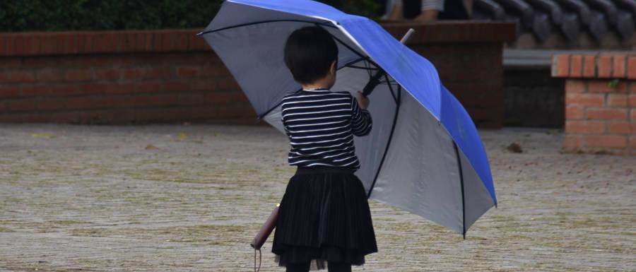 Kind mit großem blauen Regenschirm © Alexandra Menges