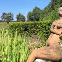 Skulptur einer nackten Frau, umgeben von Natur, an einem See © Robin Menges