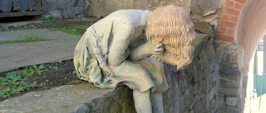 Steinfigur: ein Mädchen sitzt vornübergebeugt auf einer Mauer und hält sich eine Hand ins Gesicht. Die langen Haare verdecken das Gesicht. Oslo. © Robin Menges