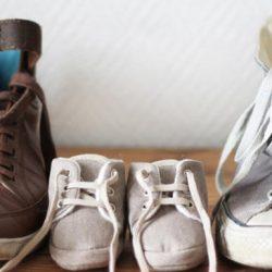 Ein Paar Babyschuhe zwischen zwei Paaren Erwachsenen-Schuhen aufgereiht © photocase.de / evamawa